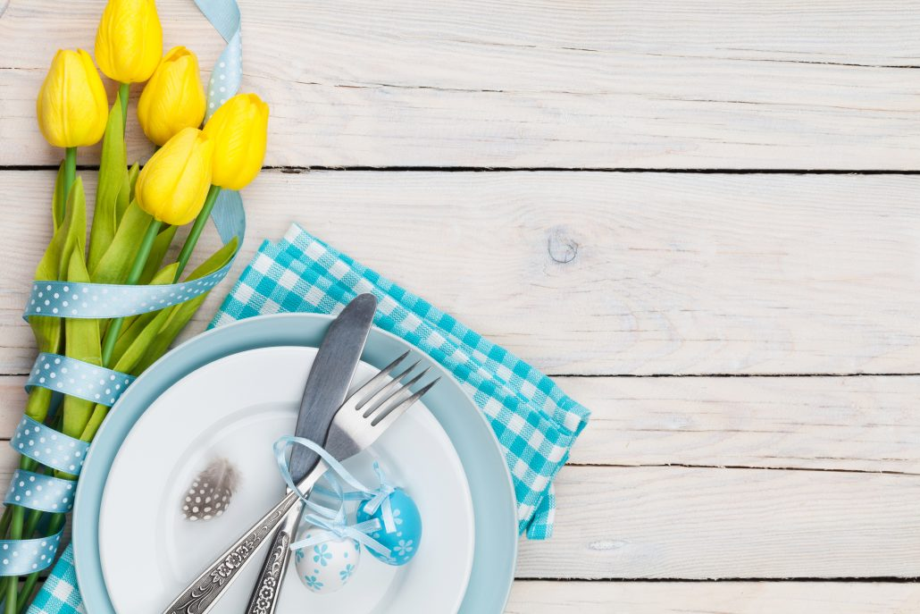 Easter with yellow tulips and colorful eggs over white wooden table. Top view with copy space